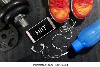 Fitness, healthy and active lifestyles concept. Dumbbells, sport shoes, smart phone with earphone and water bottle gym floor with word hiit