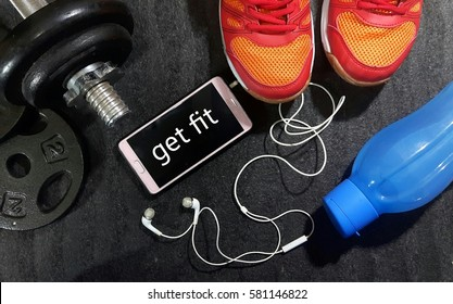 Fitness, healthy and active lifestyles concept. Dumbbells, sport shoes, smart phone with earphone and water bottle gym floor with word get fit