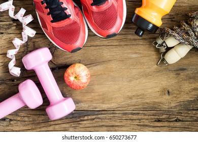 Fitness, healthy and active lifestyles Concept, dumbbells, sport shoes, bottle of waters, jump rope, measuring tape and apples on wood background. copy space, top view