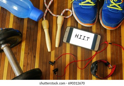 Fitness, healthy and active lifestyles concept. Dumbbells, sport shoes, smart phone with earphone, skipping rope and water bottle on wooden gym floor with word HIIT (High Intensity Interval Training)