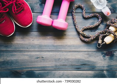 Fitness, healthy and active lifestyles love concept, dumbbells, sport shoes, bottle of waters, and jump rope  in heart shape on wood background. Top view with copy space