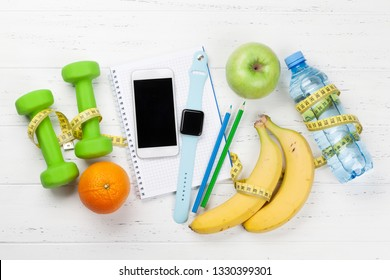 Fitness and healthy food concept. Dumbbells, fruits, smartphone and watch. Top view with copy space for your text