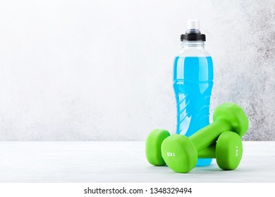 Fitness and healthy food concept. Dumbbells and drink bottle on wooden table. With copy space for your text