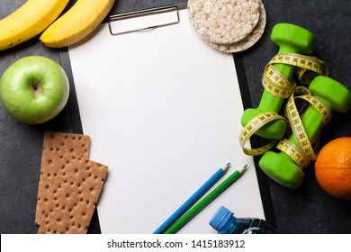Fitness and healthy food concept. Granola, dumbbells, fruits and drink bottle on stone table. Top view with copy space for your text