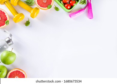 Fitness and healthy food lifestyle concept. Dumbbells, diet fruit and vegetable lunch box, water and jump rope on white background. Flatlay image, top view copy space - Shutterstock ID 1680673534