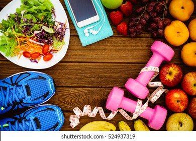 Fitness, healthy fruits, Fresh healthy salad, diet and active lifestyles Concept, dumbbells, Fresh healthy salad, fresh fruits, sport shoes, smart phone on wood background. copy space for text.