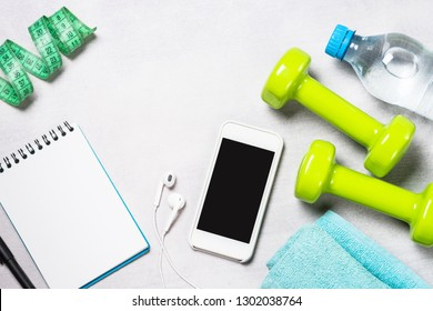 Fitness and healthy lifestyle concept. Dumbbells, measuring tape, water and smartphoneon light background. Flatlay image.