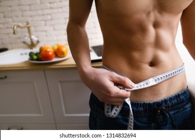 fitness, healthy lifestyle, proper nutrition, well being. athletic sporty well-formed fit man measuring his waist with tape measure, close up