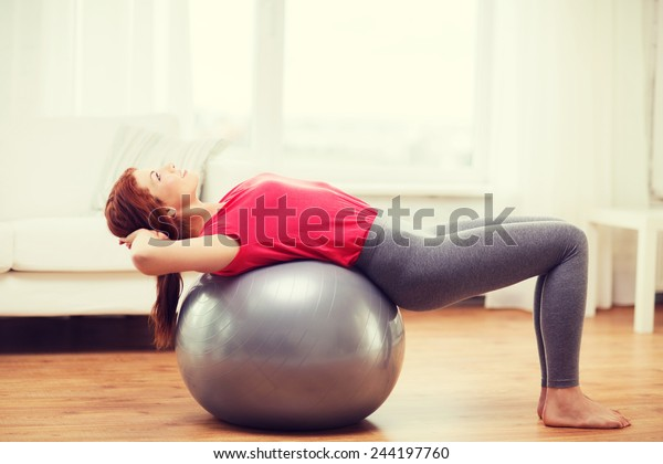 fitness, home and diet concept - smiling redhead girl exercising with fitness ball at home