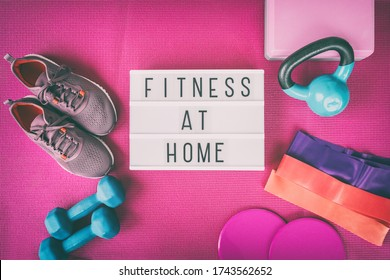 Fitness at home sign with pink yoga mat, running shoes, kettlebell weight and dumbells resistance bands and sliders for pilates online class. Exercise indoors for women.