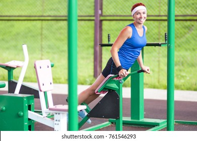 Fitness Ideas and Concepts. Concentrated Caucasian Female Athlete in Professional Outfit Having a Press-Ups Trainig for Belly Muscles. Horizontal Composition