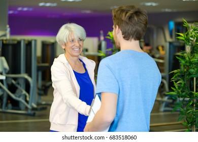 fitness instructor greeting senior woman