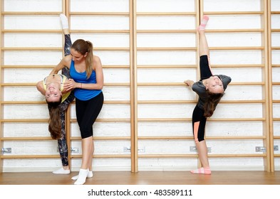 Fitness instructor helps to do exercise on an extension