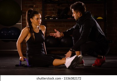 Fitness instructor instructing and encouraging the female athlete at a cross fit gym with parallette bar, calisthenics concept with handstand bar, high-intensity interval training (HIIT)