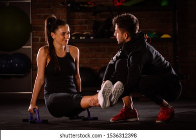 Fitness instructor instructing and helping the female athlete at a gym with parallette bar, calisthenics concept with handstand bar, high-intensity interval training (HIIT), fat burning