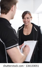 Fitness Instructor interviewing new client in gym