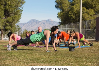 Fitness instructor leading group in push up exercises outdoors