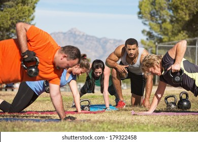 Fitness instructor with people exercising in outdoor bootcamp
