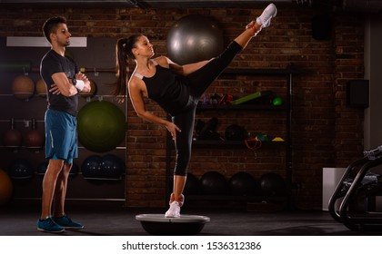 Fitness instructor supervising the female athlete in a fitness or gym exercise balancing flipped bosu ball, stay fit concept with inverted bosu, training with weights raising one leg