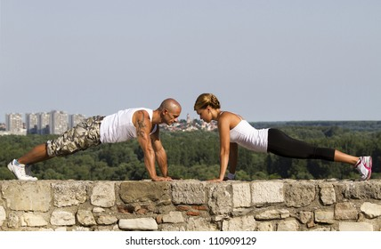 Fitness instructors doing pushups on an old stone wall. Beatiful view in bacground