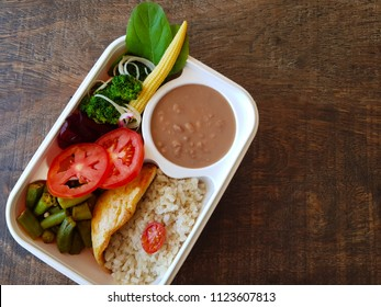 Fitness kettle, healthy food, brown rice, greens and vegetables.