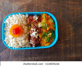 Fitness kettle with healthy food, zucchini, soybeans with tomato sauce and brown rice.