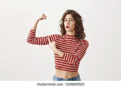 Fitness is key to beautiful body. Confident good-looking woman in cropped striped top. raising hand to show biceps, bragging how strong she is, pointing at muscle with proud expression over gray wall