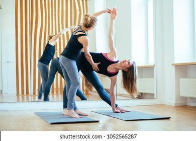Fitness lady beginning yoga practice with private teacher at home class, working out with professional female yogi instructor.