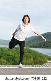 Fitness and lifestyle concept - Young asian woman short hair doing exercising outdoor and warm up preparing for jogging
