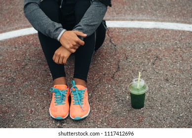 Fitness lifestyle and healthy nutrition concept. Close up of sporty woman resting and detox green smoothie.