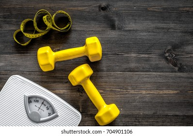 Fitness for losing weight. Bathroom scale, measuring tape and dumbbell on wooden background top view copyspace