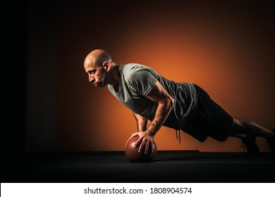 Fitness male doing push up exercise on a medicine ball, isolated against dark orange background, copy space available.