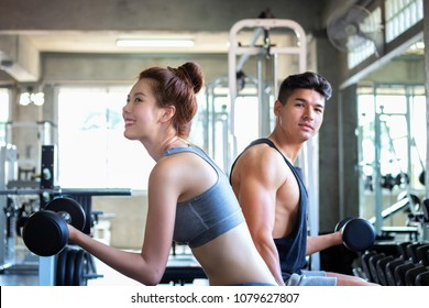 Fitness man and asian woman doing exercise and lifting dumbbell weights in sport gym, healthy lifestyle concept