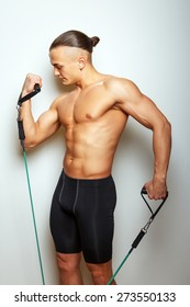 Fitness man doing exercises with expander on grey background
