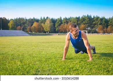 Fitness man doing push-ups on the grass. Sports and active lifestyle.