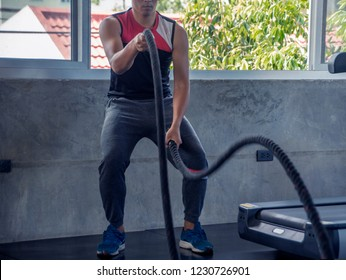 Fitness man exercising with ropes at gym. man  rope workout working out arms and cardio for cross fit exercises.