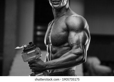 Fitness man in gym drinking water after workout. Fitness and bodybuilding healthy background. Caucasian man doing exercises in gym. Water bottle and supplements nutrition concept