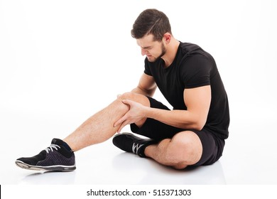 Fitness man injured. in studio. knee injury. isolated white background