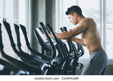 Fitness man with pants cardio workout on cardio machine in sport gym