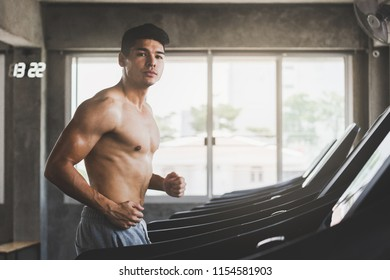 Fitness man with pants running on treadmill machine in sport gym