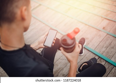 Fitness man runner using smart phone texting instagram activity tracking. Active male jogger sitting on stairs.