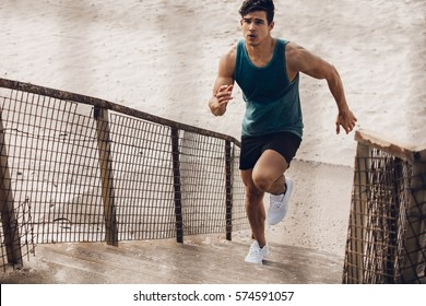 Fitness man running up the steps on beach. Muscular young male runner working out on steps on sea shore.