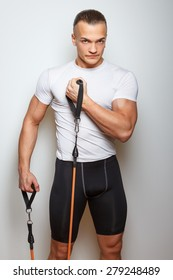 Fitness man in sportswear doing exercises with expander on white background