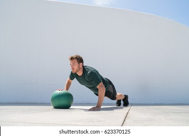 Fitness man strength training pushup chest and shoulder muscles doing alternating single arm medicine ball push-ups floor exercises at outdoor gym.