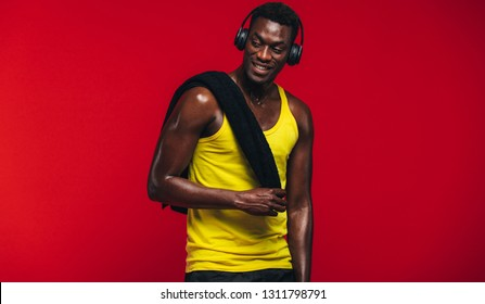 Fitness man with towel on shoulder listening to music on headphones. Fit young man resting after from workout on red background.