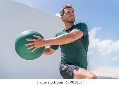 Fitness man training at gym working out legs and abs doing lunges twisting the torso for core workout with medicine ball weight. Full body workout.