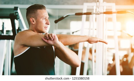 Fitness man warming up in gym. Female doing warmup stretching workout on Gym background.