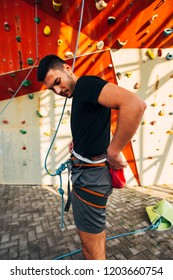 Fitness man while preparing for bouldering on artificial wall