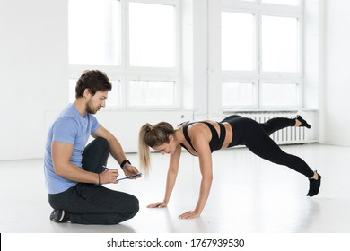 Fitness man and woman during calisthenic workout with in the gym.