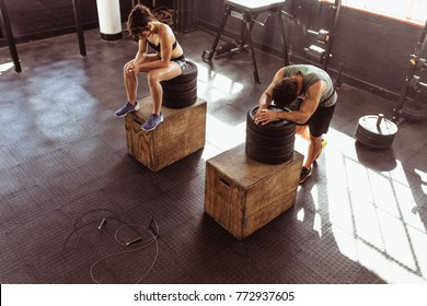 Fitness man and woman resting on box after exercises in cross training gym. Young people in the gym resting after heavy workout. Taking a break after intense physical training session.